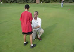 instructor giving golf lesson to student